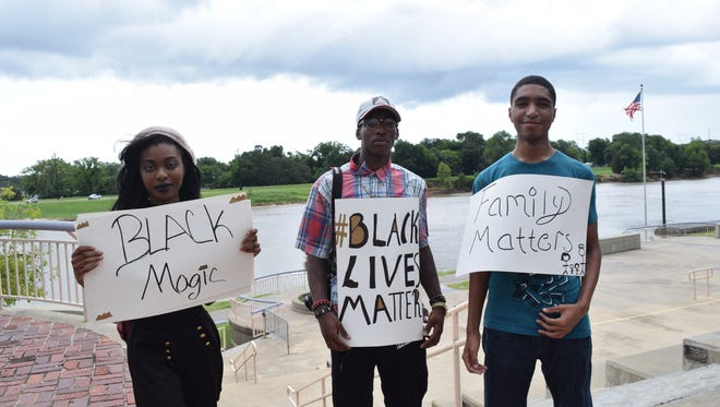 Daisha Broomfield, Isaiah Bryant and Kyle Bridgewater hold signs during a peaceful Black Lives Matter rally Sunday at the Alexandria Levee Park Amphitheatre. Bryant said the rally was a call for unity and justice in light of the recent officer-involved shootings around the country.