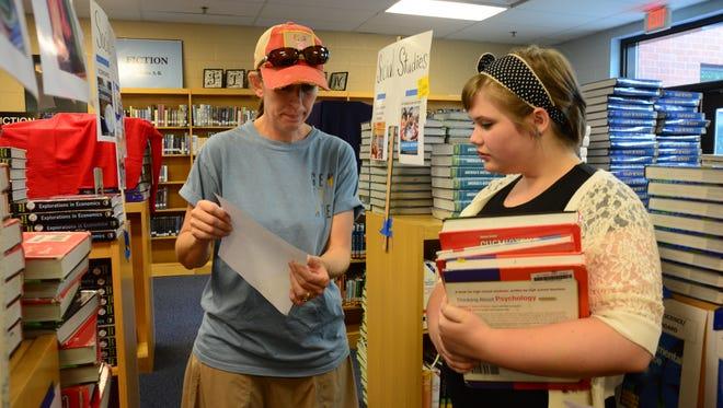 Parent volunteer Rebecca Jester helps incoming Centennial High sophomore Carol Klinedinst locate textbooks.