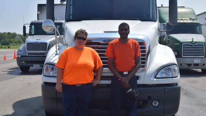 Students stand in front of the truck they are learning to drive. April Webb (left) and Raheem Underwood (right).