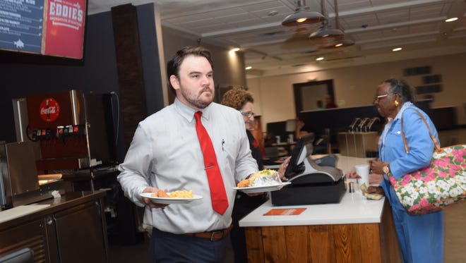 Drew Jones, bar manager at the newly renovated Holiday Inn located in downtown Alexandria, helps deliver orders at lunchtime at the new Eddie's Smokehouse and Seafood Restaurant which is located in the hotel.