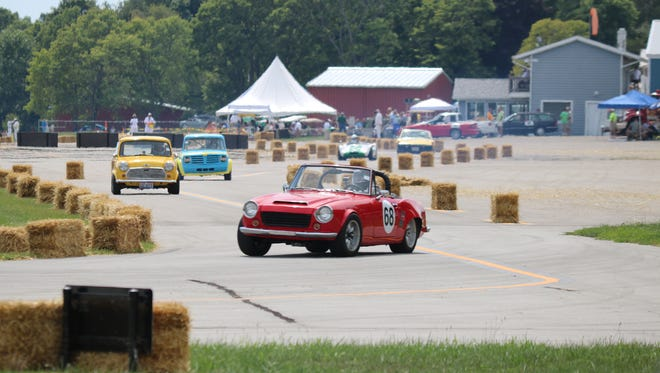 Drivers make one of the first sharp turns of the track on the airport in their vintage sports cars during the Put-in-Bay Road Races Reunion on Tuesday.
