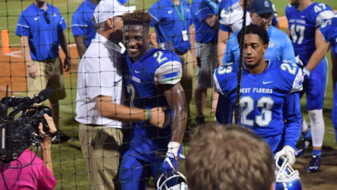 UWF football coach Pete Shinnick hugs linebacker Andre Duncombe, a freshman from Miami, who forced and returned a fumble, following team's win Saturday night at Blue Wahoos Stadium.