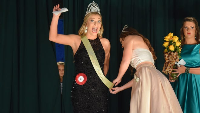 Miss Corn Festival Joshlyn Black raises her hand in celebration after being crowned Queen.