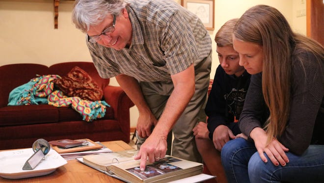 Brian Koenig points out Pam in an old running picture while going through photo albums with his kids, Paul and Liz. Pam, who died in 2011 after a battle with breast cancer, was honored at this year's Komen Northwest Ohio Race for the Cure in Toledo.
