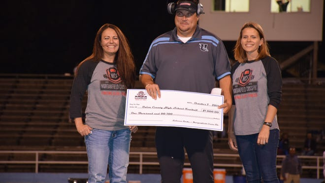 Gym representatives Rebecca Burke (owner/trainer) and Amanda Davis presented a check in the amount of $1000.00 to Coach Derek Johns and UCHS Braves at Friday night's home game against Fort Campbell.