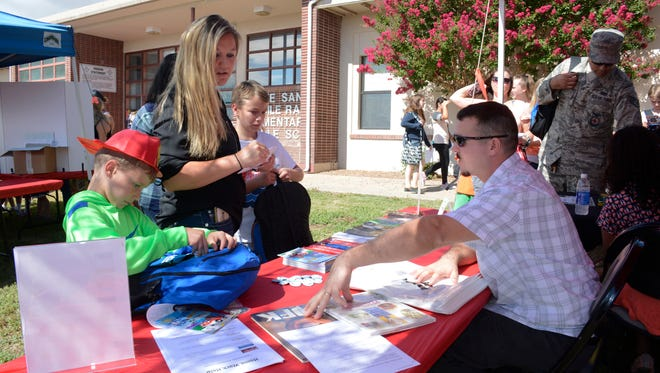 """WSMR Librarian Colin O'Hanlon provides resources for an upcoming research paper to White Sands School parent Lavina Brock and her children during a first day of school holiday, Aug. 11. The school recently received an """"A"""" grade from the New Mexico Public Education Department."""