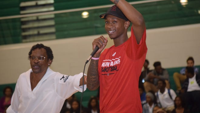 Peabody's Cedric Russell Jr. (right) committed to attending the University of Louisiana at Lafayette Friday during a pep rally held at the school. His father Cedric Russell Sr. is to the left.