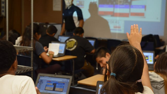 A student raises her hand to ask a question in Russell Eves' eighth grade U.S. History class at Nellie Coffman Middle.