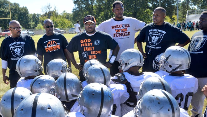 Orange Mound Raiders junior football team with Coach T (center) and the other assistance coaches at their final game of the season.