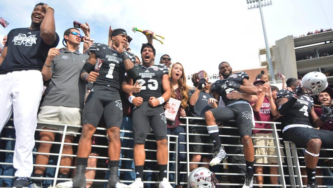 Mississippi State players celebrate with fans after the upset of No. 4 Texas A&M on Saturday in Starkville.