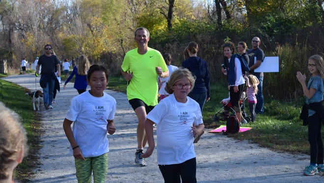 Adah Clark, left, and Meredith Russell finish a 5K run as part of Running Girl, a club launched in memory of the ISU women's cross country team who died in an airplane crash in 1985.