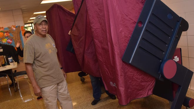 Norman Thomas prepares to go cast his voting Tuesday at precinct C30 located at Nachman Elementary School.
