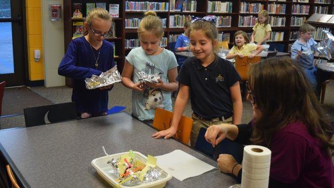 Krista Duke, Macy Gough, Gracie Lewis, and Haley Lewis wait to see if their boats can withstand the weight of pennies.
