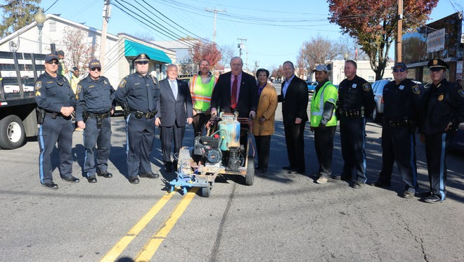 Parsippany Mayor James Barberio, center, with members of the township council and police force about to paint a blue line along North Beverwyck Road in downtown Lake Hiawatha to honor police.