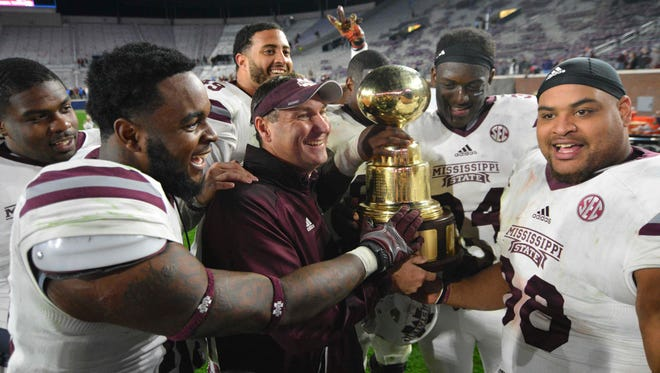 Mississippi State Bulldogs head coach Dan Mullen and players celebrate  with the Egg Bowl trophy after the game against the Mississippi Rebels at Vaught-Hemingway Stadium. Mississippi State won 55-20.