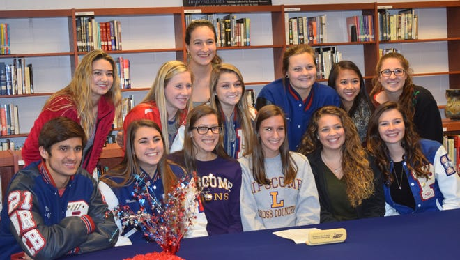 Pace High senior Haley Kling (seated center, gray pullover) is joined by fellow members of the Patriots cross country team and friends after reception Friday to honor her signing at Lipscomb University.