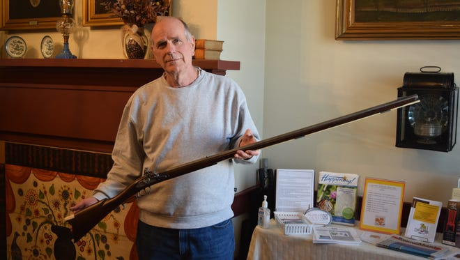 Terry Peterman holds a replica of  Kentucky long rifle that he crafted for the new entrance exhibit to the Oldham County History Center when it re-opens on Jan. 7.