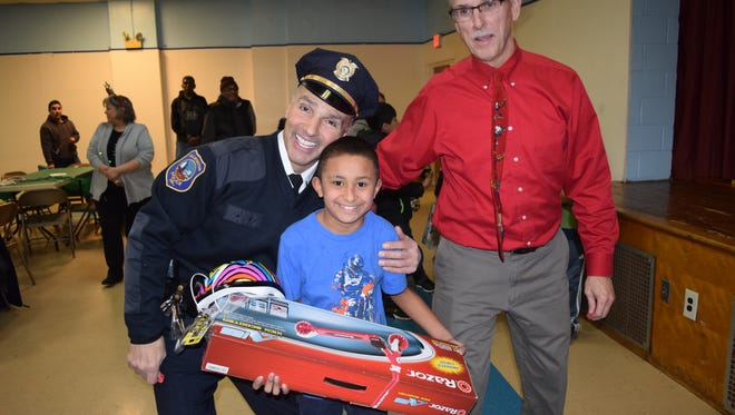 Luis Romero holds his newly-won scooter with Lt. Gregory Ciotti (left) and Kevin Kelley (right) on Tuesday, Dec. 20.