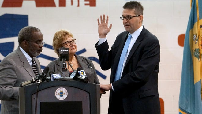 Judge Charles H. Toliver (left) administers the oath of office to Matt Meyer during his inauguration in January.