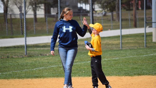 Gavin Trautman, 9, of Logan high-fives his helper, Faviana Cohen, 13, of Vineland during a  North Vineland Little League Challenger League game last season. Registration for this season is in progress.