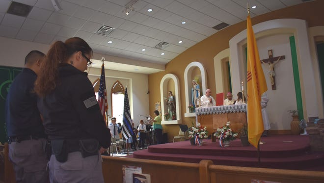 Officers bow their heads in prayer on Friday during the Blue Mass, a Catholic mass held at Immaculate Conception Church. The mass honored local police, fire and first responders.