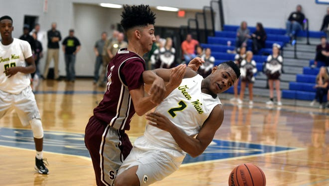 Station Camp's Jalen Woods collides with Gallatin's Zyun Mason during Friday's District 9-AAA Tournament quarterfinals.