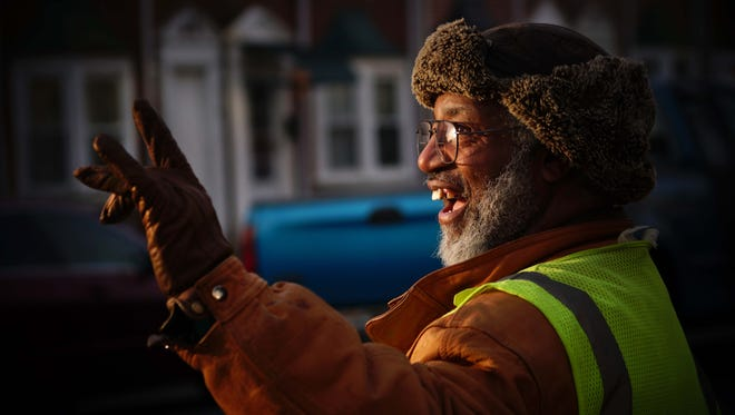 Earl Tate, 66, a volunteer crossing guard for over 19 years, gives friendly waves to motorists and children on the corner of 26th and Jessup Street.