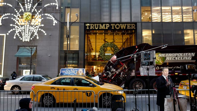"""In this Dec. 2, 2016, file photo, a television news correspondent, right, reports live from Trump Tower in New York. Long before he tweeted about wiretaps, President Donald Trump was worried about who was listening in on his calls. The president claimed in a series of early morning tweets over the weekend that his predecessor had ordered that his phones in Trump Tower be monitored in October, suggesting that """"a good lawyer could make a great case"""" out of it."""