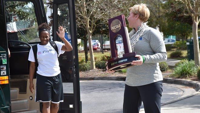 UWF coach Stephanie Yelton clutches NCAA trophy last year as players exit bus trip from St. Petersburg where Argos won the NCAA South Region championship.