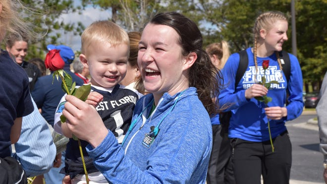 Senior point guard Alex Coyne is greeted by her nephew after she returned with the UWF women's basketball team Tuesday from winning the NCAA South Region championship