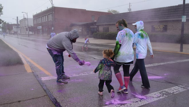 Volunteer Brian Eickhoff throws color onto Color Me Fun Run Participants on Franklin Street Saturday morning.