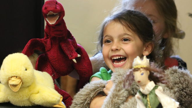 Ellie Thomas laughs while putting on a puppet show during her trip to the library.
