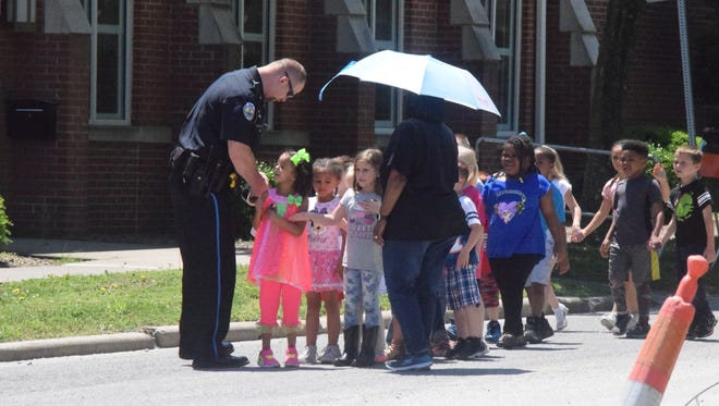 Police chief Geoffrey Deibler hands out stickers as the kindergartners from Morganfield Elementary make their way to the library.