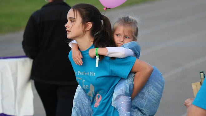 Emma Floyd carries Rese Buckman on her back as they watch as several participate in the Survivor Lap.