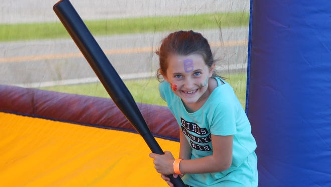 Brylee Jackson smiles after taking a swing at an inflatable bouncy house batting cage. The event featured several activities for kids of all ages to enjoy.