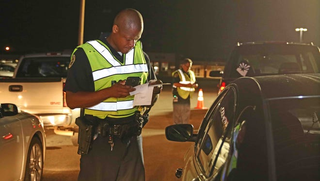 Officers conduct a DUI checkpoint on US Highway 41A near the Tennessee/Kentucky state line on Friday.