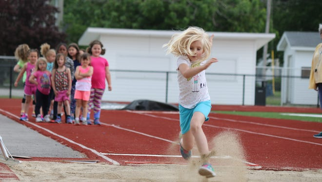 Elli Abraugh, kindergartner at Bataan Primary School, performs in the long jump event during the annual Olympic Day on Wednesday.