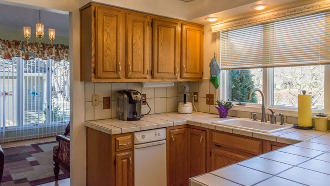 This townhome has a kitchen with granite-tile counters, with a sun-room beyond it where you can enjoy golf-course views.