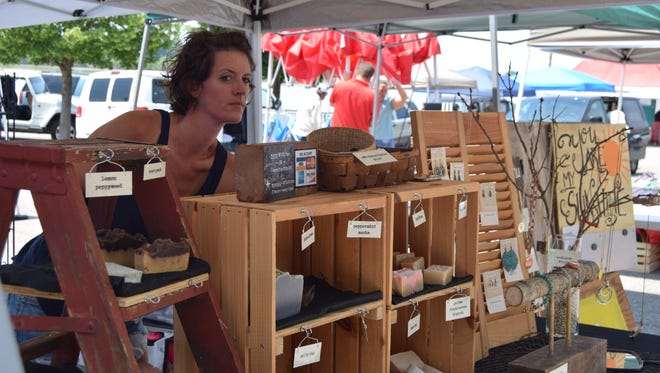 Bethany Jahn stands by her products, including soap, lip balm, jewelry and wall art, at the Newburgh Farmers' Market Saturday.