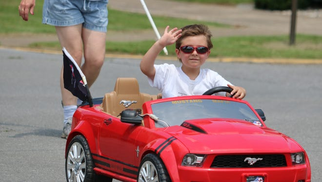 Chase Elsey waves while driving his mustang through the Sturgis Trade Days parade.