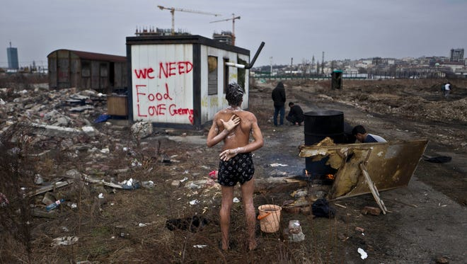 A 14-year old unaccompanied minor, a migrant from Afghanistan, showers near an old train car where he and other migrants took refuge in Belgrade, Serbia, in this file photo from Feb. 11, 2017.