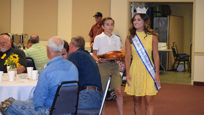 Miss Union County Fair, Tori French is followed by Collin Nalley as they show one of the hams up for auction to potential bidders.