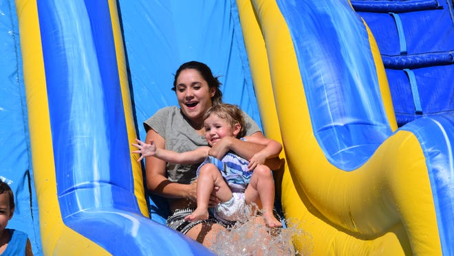 Rachel Berry and her daughter Ansleigh slid down the water inflatable ride set up at the Uniontown River Days