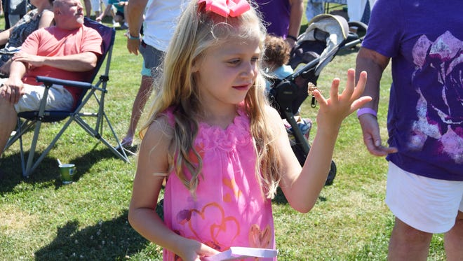 Kendall Edwards, 7, releases a butterfly in memory of her uncle at a Project Reveal event Saturday morning.
