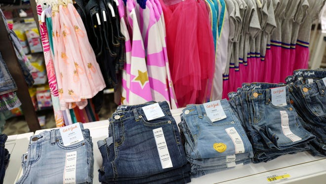 In this Friday, July 14, 2017, photo, Cat & Jack jeans, foreground, appear on display at a Target store in New York. The jeans are made with Repreve polyester fabric, created from recycled plastic bottles. For this year's back-to-school shopping season, green is the new black. Increasingly, parents and their kids are looking for second-hand clothing or fashions made from reused material.