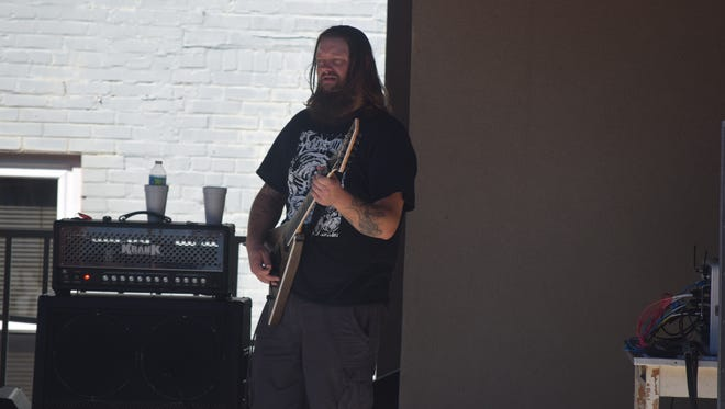 A member of one of the many bands plays his guitar.