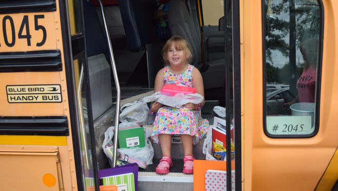 Lilly LaBelle, a 6-year-old heading into the first grade, sits with donated items at LCS's Stuff the Bus school supply drive.