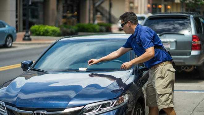 Mark Horn, a parking enforcement officer for the Downtown Improvement Board, tickets a car for parking in the wrong direction on Palafox Street.