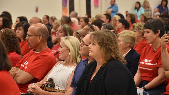 Santa Rosa Professional Educators member David Godwin, left, a math teacher at Pace High School, listens during a special school board meeting Thursday, Aug. 10, 2017, at Bennett Elementary School in Milton on whether teachers will receive retroactive pay raises.