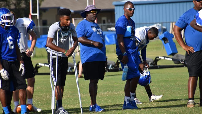 Injured receiver Caleb Ward (on crutches)  watches with his father, Charlie Ward, as the Washington Wildcats go through an early August practice.